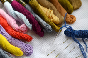 colored thread for embroidery and needles on canvas