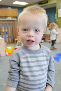 A boy smiles at the camera in the Children's Learning and Care Center