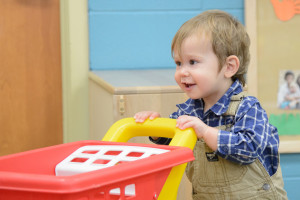 A toddler pushes around a toy shopping cart the the Children's Learning and Care Center