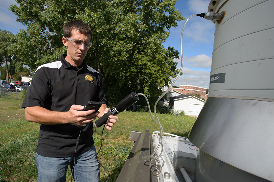 Staff testing gas quality at campus AD system
