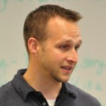 A young gentleman is looking away from the camera at someone and is in front of a whiteboard.