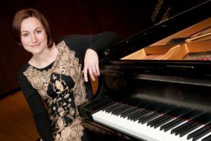 UWO student Rebecca Ottman sitting on a piano bench.