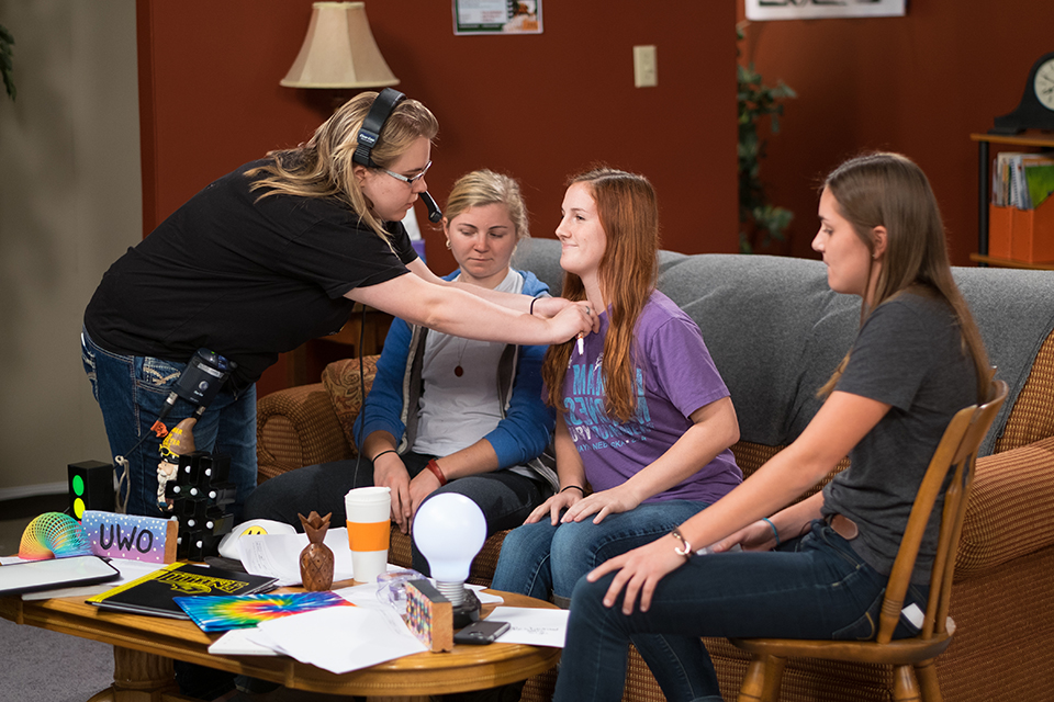 4 students work on the set of a multi-camera studio production.
