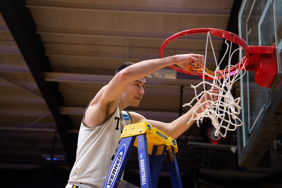 Adam Fravert cutting a piece of net.