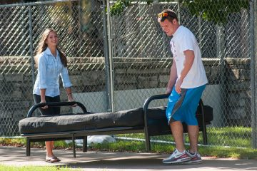 A male and female student carry a futon on the UWO campus