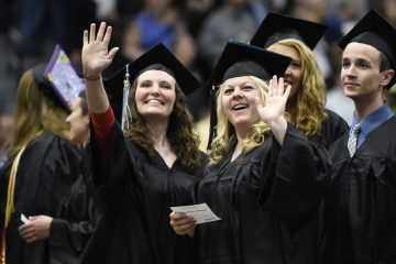 Graduates wave to family and friends at the University of Wisconsin Oshkosh spring commencement