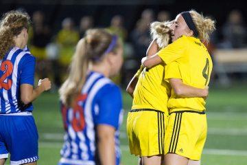 Robyn Elliott hugs her sister Rachel after her twin scores a goal.