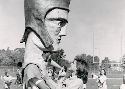 1974: A cheerleader greets mascot Tommy the Titan during a football game.